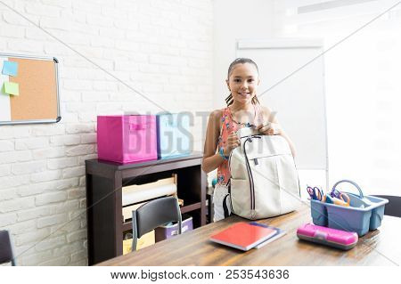 Smiling Preadolescent Girl With Backpack Standing At Table In House