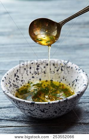 A homemade salad dressing with olive oil, chopped herbs and aromatic spices pours from a spoon into a bowl on a gray wooden background.