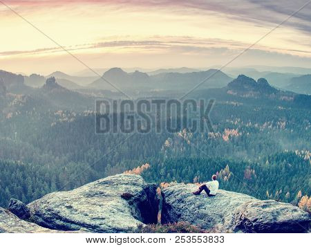Sit On Peak. The Tired Out Tourist Has Reached The Rocky Peak Of The Mountain And Now Enjoys Amazing