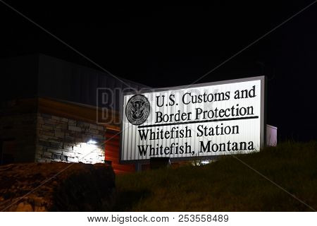 WHITEFISH, MONTANA, USA - August 13, 2018:  United States Customs and Border Protection, Whitefish Station, sign illuminated at night.