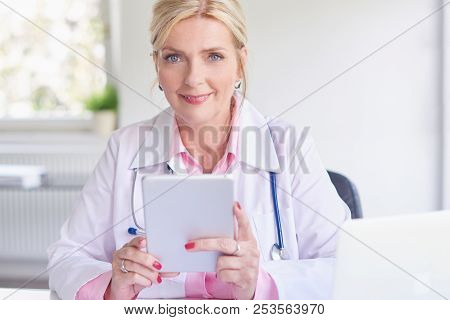 Female Doctor Using Toucpad At The Private Clinic