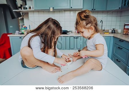 Two Little Girls In The Kitchen Sitting On The Table.