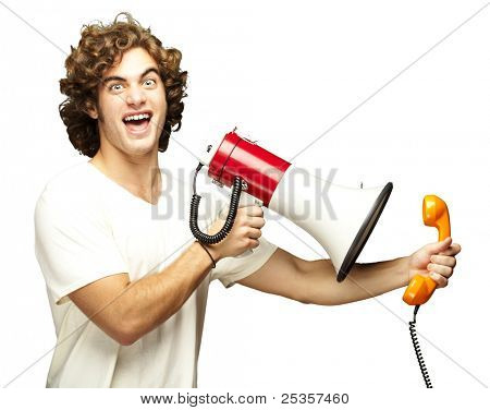 portrait of young man shouting with megaphone and talking on vintage telephone over white