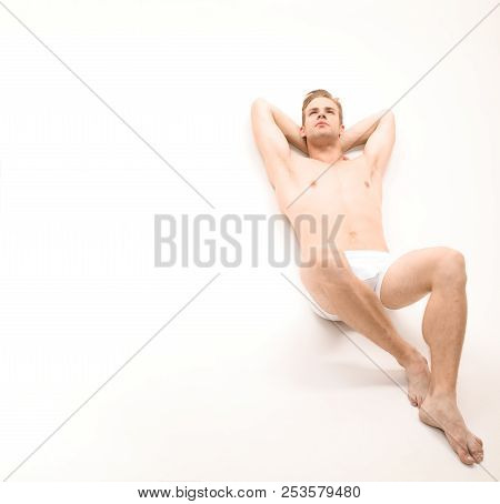 Handsome Sexy Naked Man Lying On White Background. Sexy Man In Underwear. Muscular Male Model In Tre
