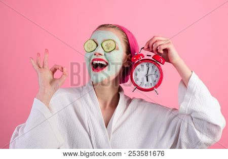 Cosmetic Procedures. Woman With Cosmetic Mask On Face Holds Clock. Natural Ingredients. Wellness And
