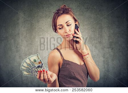 Young Confident Woman Speaking On Smartphone Being Careless About Price For Roaming Holding Pile Of