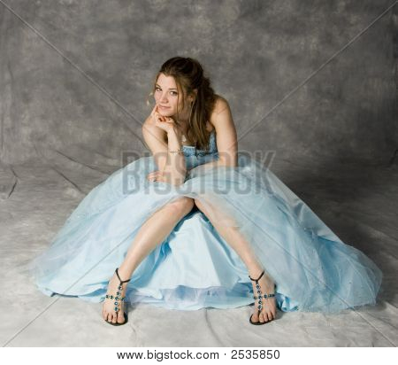 tennage girl seated wearing blue prom dress on gray studio background poster