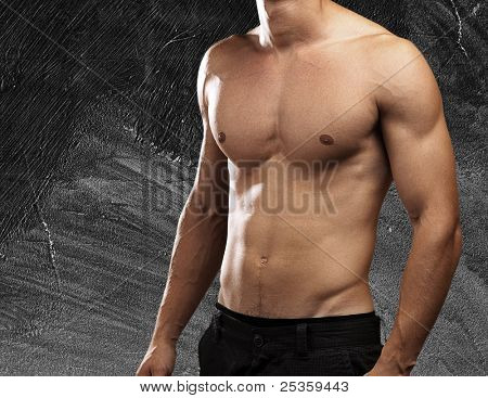 strong torso of young man against a grunge wall