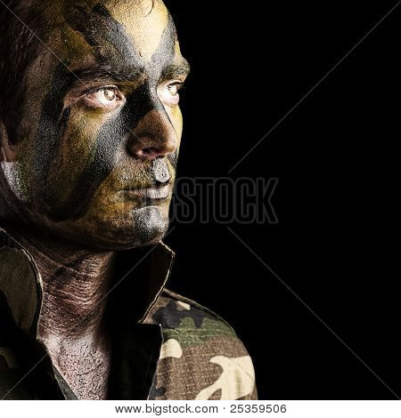 portrait of young soldier face with jungle camouflage against a black background