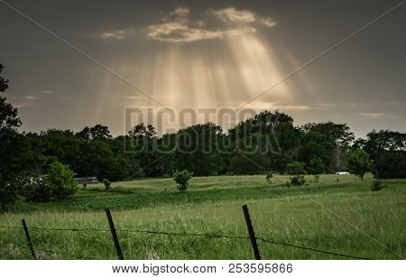 Rays Burst Through Storm Clouds Over Pasture