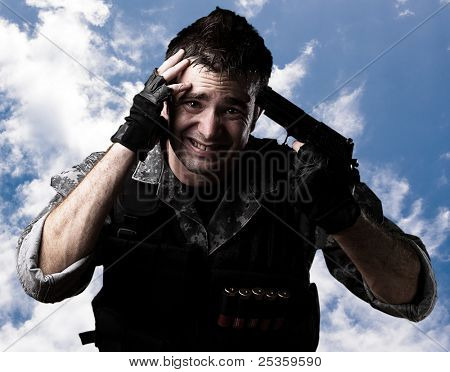portrait of young soldier gesturing suicide against a cloudy sky background
