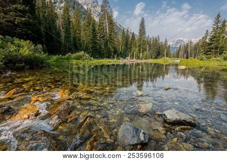 Smooth River Flows Through Cascade Canyon In Wyoming Wilderness