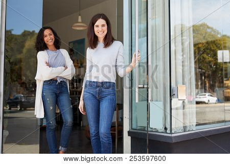 Female business owners in the doorway of their coffee shop