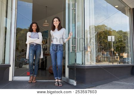 Two young female coffee shop owners stand outside their shop