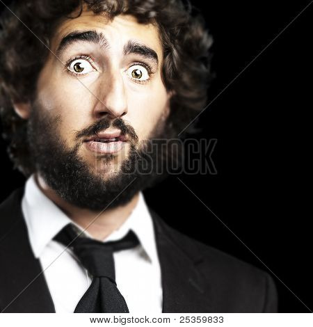 portrait of young business man surprised against a black background