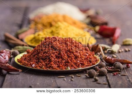 Heaps Of Various Ground Spices On Wooden Background. Georgian Spices, Indian Spices, Arabian Spices