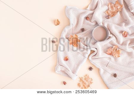 Autumn Cozy Composition. Cup Of Coffee, Women Fashion Sweater, Dried Leaves On Pastel Beige Backgrou