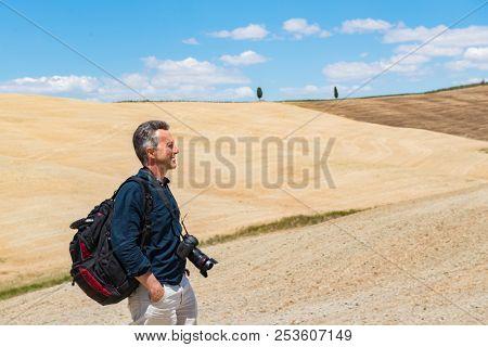 Man professional photographer with digital camera walking in tuscany fields. Tuscany holidays. Italy holidays tuscany.