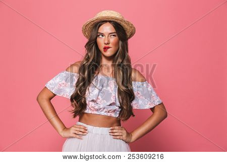 Portrait of seductive european woman 20s wearing straw hat biting lips and holding arms on waist isolated over pink background in studio poster