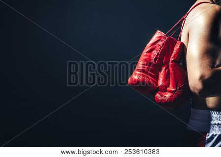 Pair of red gloves on the fighter's back. Boxing equipment. Close-up.