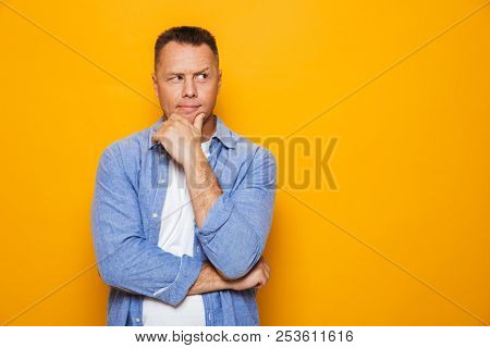 Portrait of a pensive middle aged man isolated over yellow background, looking at copy space