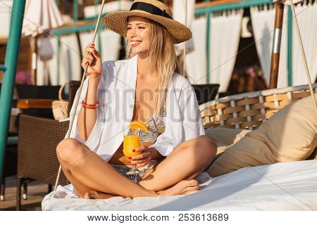 Photo of gorgeous woman 20s in straw hat smiling and holding orange juice while sitting on luxury sofa on beach during summer sunny day poster