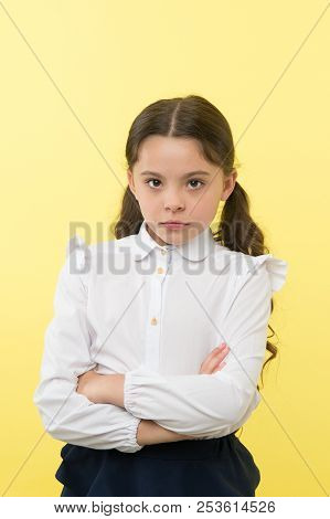 She Does Not Agree With You. Girl Serious Face Offended Yellow Background. Kid Unhappy Looks Strictl