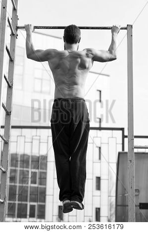 Man Do Chin Ups Outdoor. Sportsman Pull Up On Stadium. Athlete With Fit Torso And Strong Hands On Ba