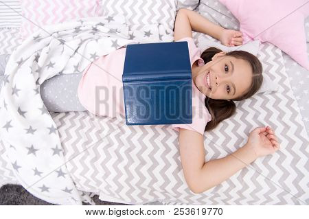 Reading Concept. Happy Child Reading In Bed. Little Girl Enjoy Reading Book. Reading Is Fun