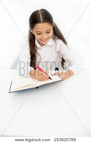 Little Bookworm. Writing Notices. Girl Child Writes Hometask While Sit Table White Background. Schoo