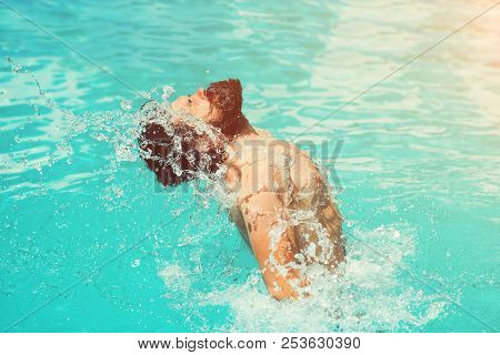 Young Man Splashing Water By His Wet Hair And Beard On Face Having Fun In Swimming Pool In Summer. S