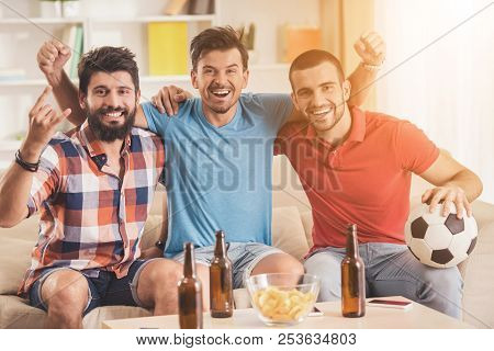 Happy Friends Sitting On Sofa Watching Football. Friends On Party. Weekend At Home. Three Happy Frie