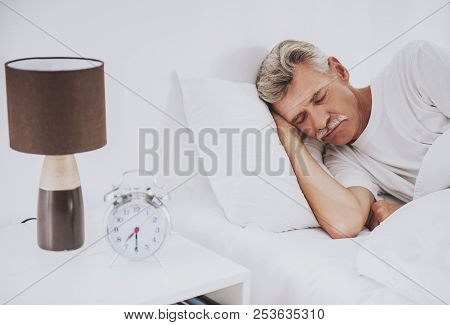 Old Man Sleeping In Comfortable White Bed At Home. Rest Roncepts. Resting At Home. White Bed. Health