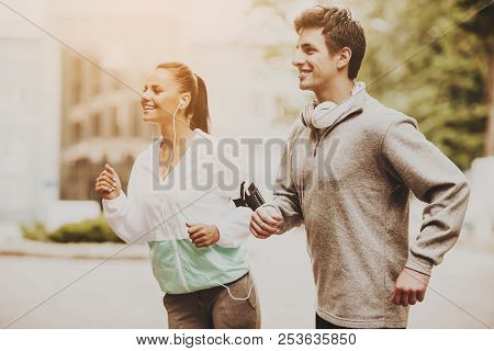 Young Happy Couple During Jogging In Morning. Healthcare And Active Lifestyle Concept. Morning Exerc