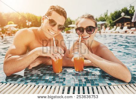 Young Smiling Couple In Swimming Pool In Summer. Leisure In Summer. Relaxation For Family Outdoor. V
