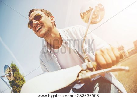 Smiling Young Man Riding On Scooter Along Street. Young Man In Sunglasses. Travel On Summer. Casual