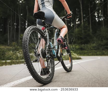 Young Woman Riding On Mountain Bicycle On Forest Road. Bike On Road. Biker Competition. Recreation A