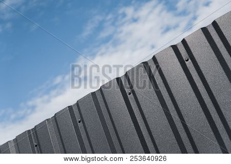metal plate against blue cloudy sky. Siding. Seamless surface of galvanized steel. Industrial building wall made of corrugated metal sheet, flat background photo texture. poster