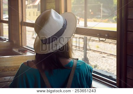 Girl in vacation. Traveler girl watching through train window. Young traveler girl in vacation. Girl traveling by train in vacatio. Traveler girl observing landscape through window. Travel. Girl. Train. Traveler. Vacation