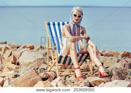 Elegant Fashionable Girl In Vintage Swimsuit Sitting In Beach Chair On Rocky Shore