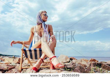 Elegant Woman In Retro Swimwear Sitting In Beach Chair On Rocky Shore