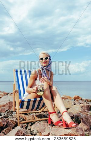 Beautiful Elegant Girl In Sunglasses Holding Jar With Cocktail And Relaxing In Beach Chair On Rocky