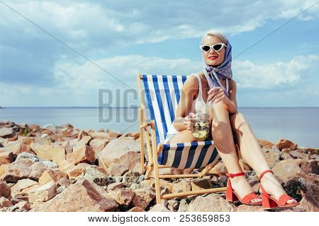 Elegant Stylish Girl Holding Cocktail And Relaxing In Beach Chair On Rocky Shore