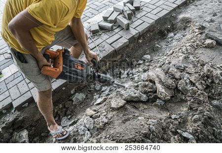 Workers use Electric Concrete Breaker. Male worker repairing driveway surface with jackhammer, digging and drilling concrete roads during sidewalk construction works. poster