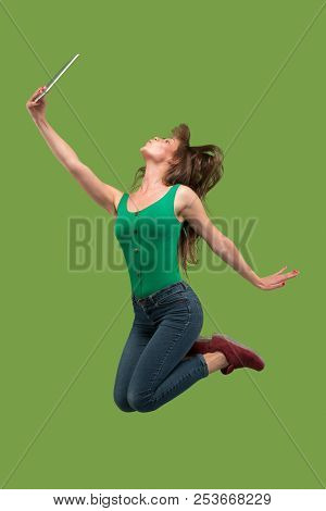 Jump Of Young Woman Over Green Studio Background Using Laptop Or Tablet Gadget While Jumping. Runnin