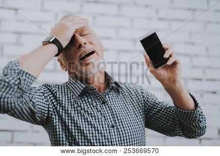 Old Man With Broken Mobile Phone Holding Head. Electronic Devices Concept. Mobile Device Hardware. M
