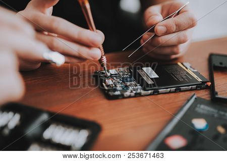 Close Up. Young Man Repairing Mobile Phone On Desk. Repair Shop. Worker With Tools. Magnifying Glass
