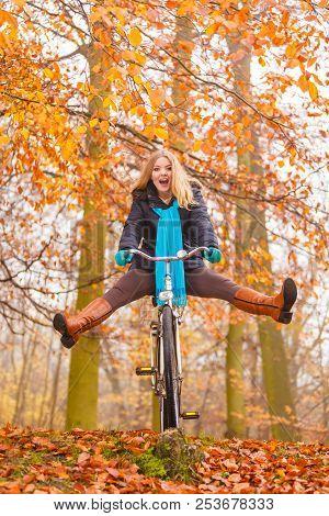 Active Woman Having Fun Riding Bike In Autumn Park