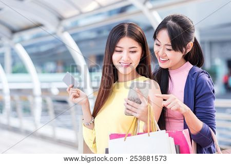 Happy Beautiful Young Woman Enjoy Shopping And Hold Paper Shopping Bag And Mobile Phone In The City
