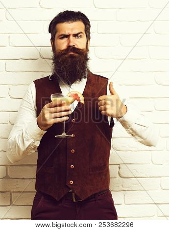 Serious Face Holding Glass Of Alcoholic Beverage In Vintage Suede Leather Waistcoat On White Brick W